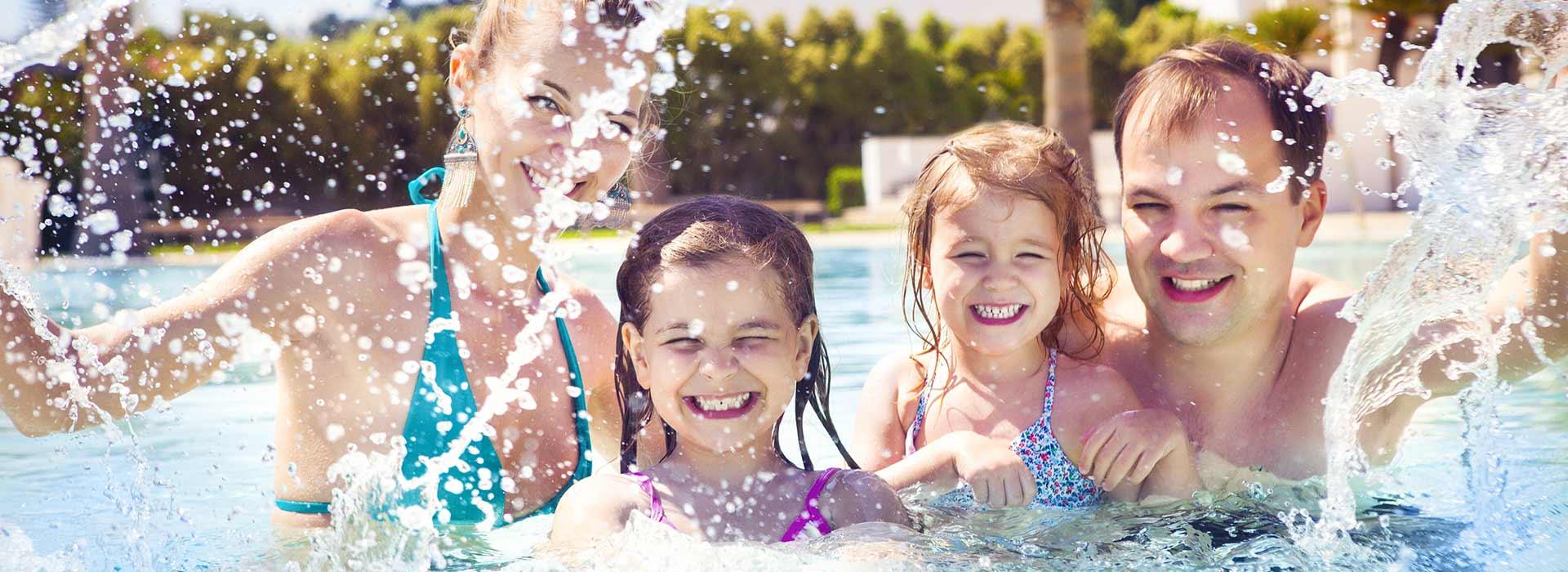 Une famille en train de rire, s'éclaboussant dans la piscine.