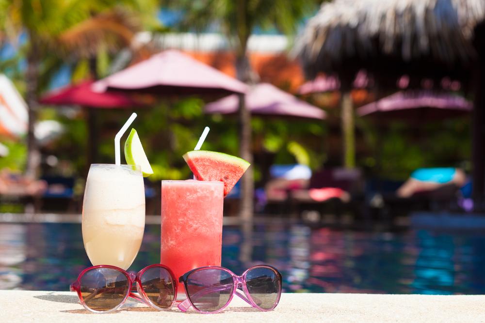 Deux cocktails posés sur le rebord de la piscine.