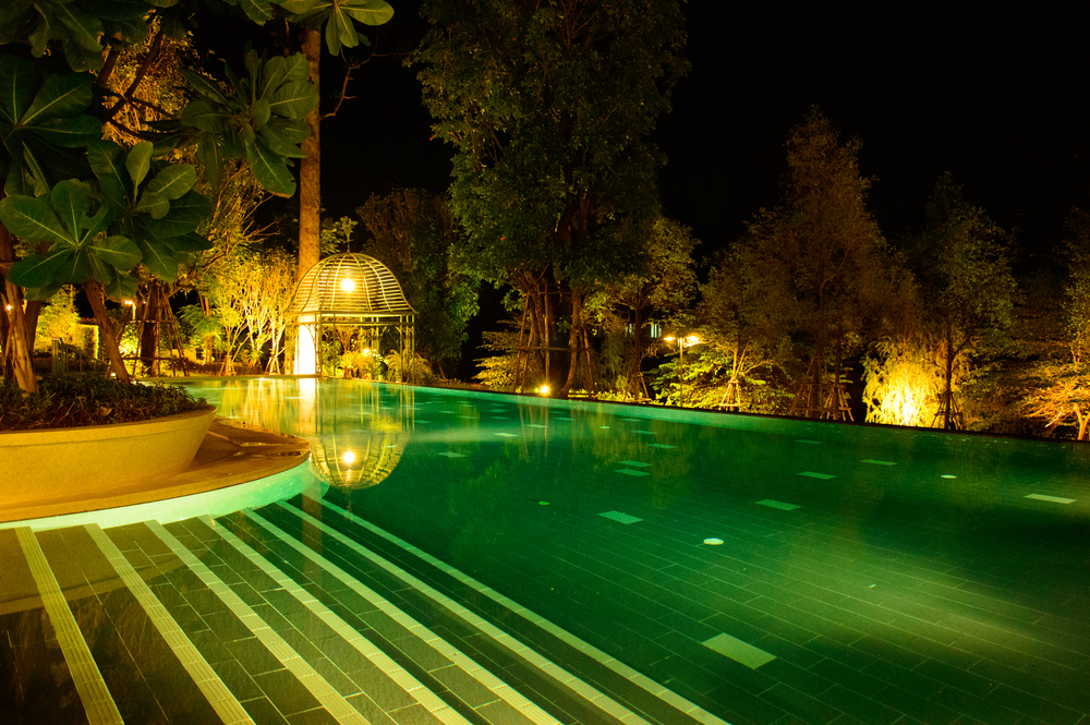 Piscine teinte en vert, la nuit, entourée de lumières diverses.