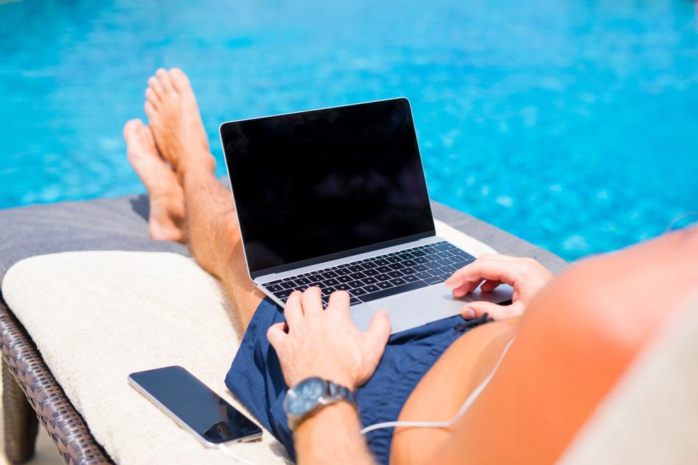 Homme en train de surfer sur le web au bord de sa piscine.