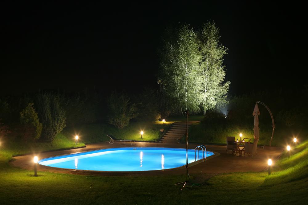 Piscine de nuit, éclairée par des lumières dans le jardin.
