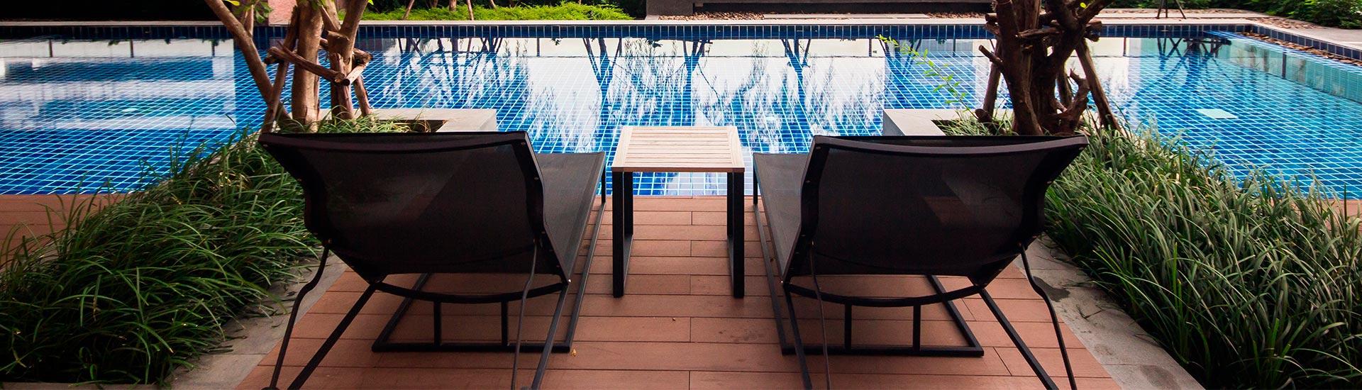 Deux transats en bois face à une piscine.
