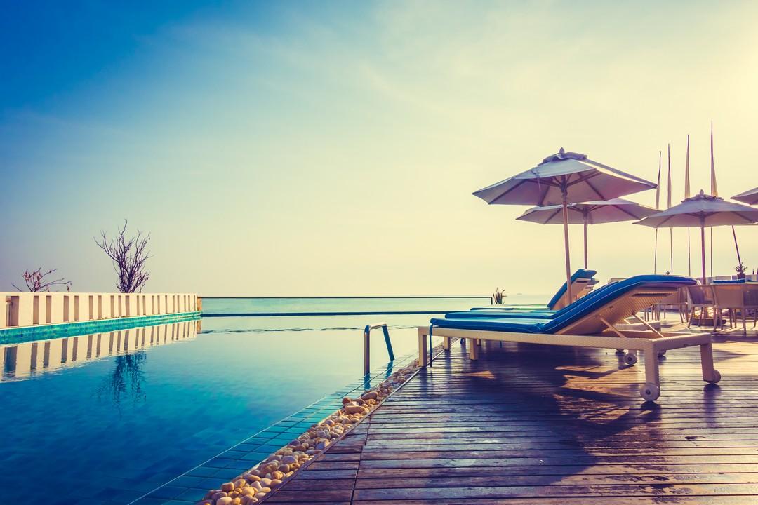Transats en bois au bord d'une piscine au soleil couchant.
