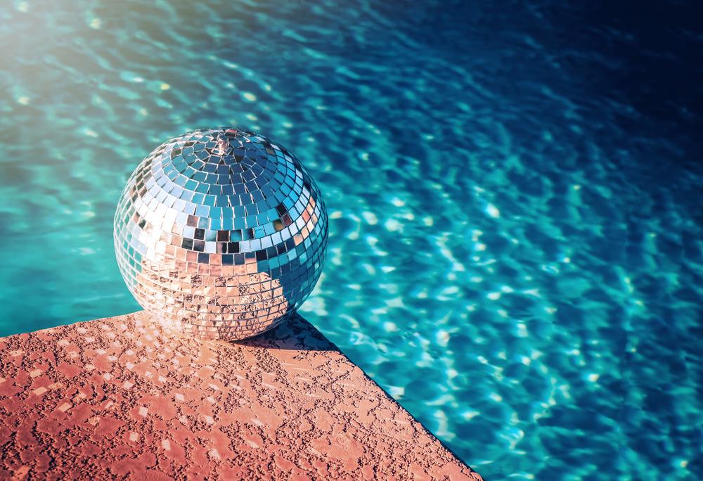 Une boule à facette au bord d'une piscine.