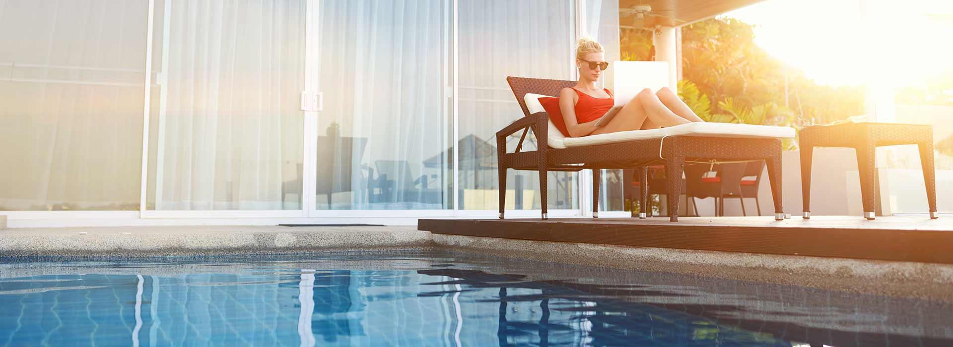 Femme allongée sur un transat en train de lire, près d'une piscine.