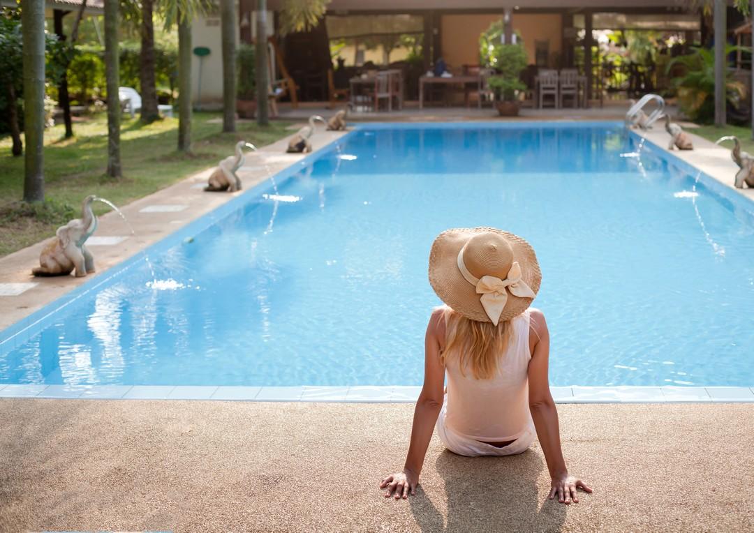 Femme assise au bord d'une piscine.