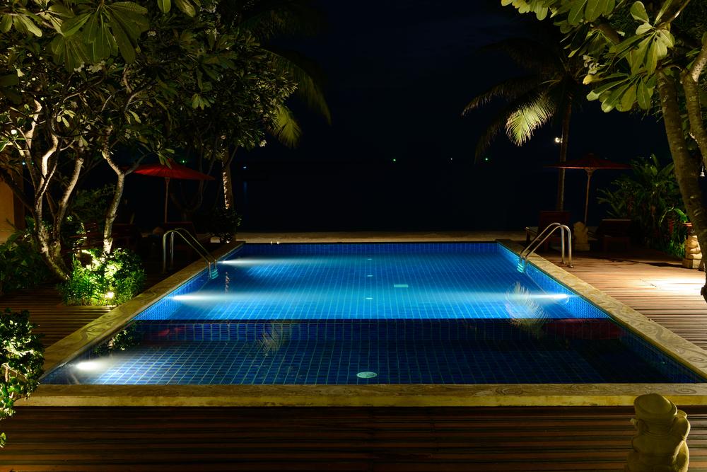 Piscine de nuit, éclairée par des lumières sous-marines.
