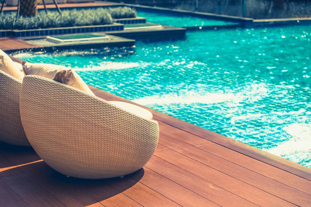 Petits sièges en osier près d'une piscine.